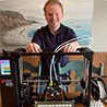Man stands behind 3D printer, which holds Ear Saver mask clips for frontline medical workers.